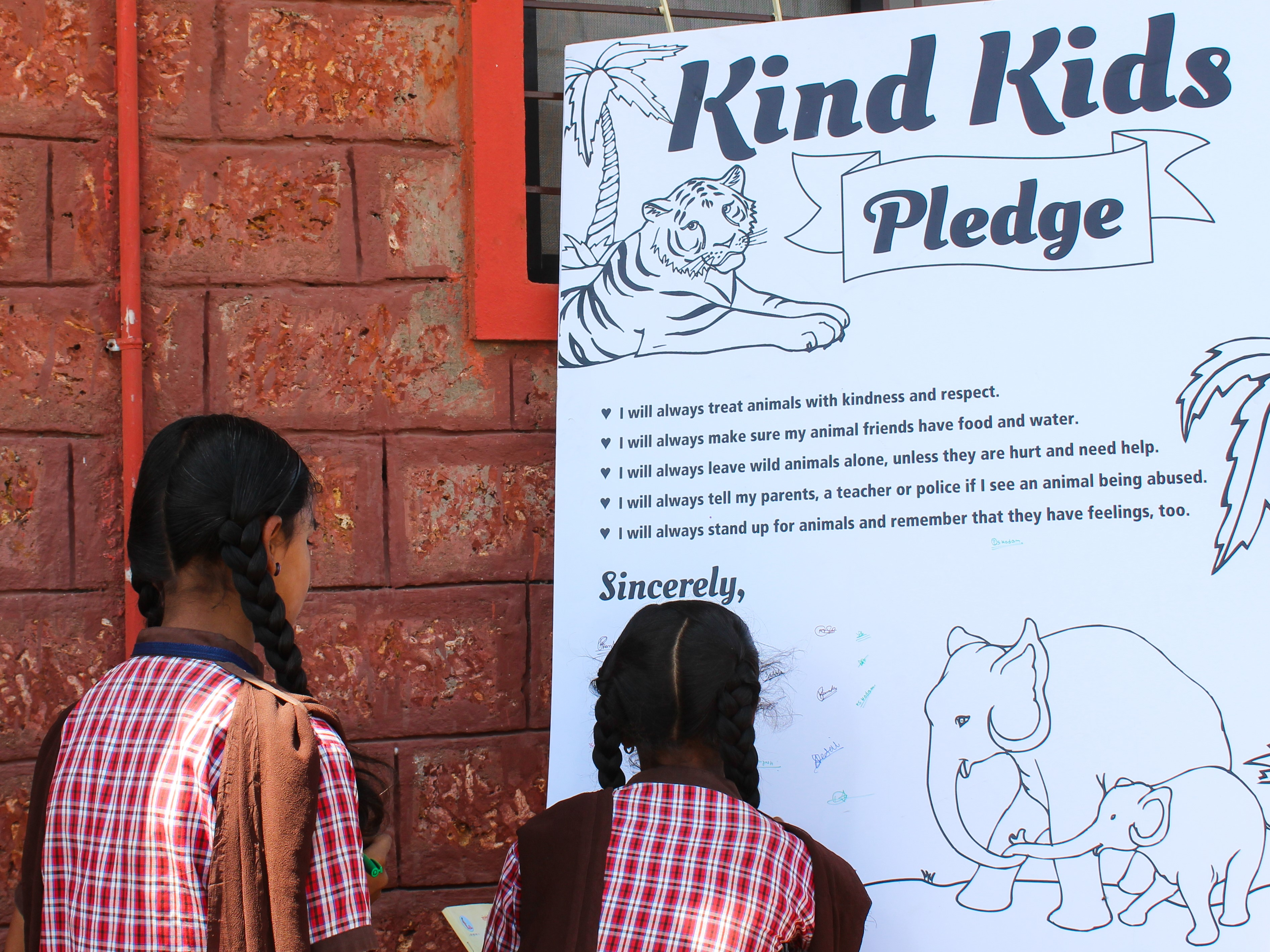"""Two students sign their names to the """"Kind Kids"""" pledge poster."""