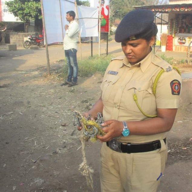 A police officer looks disapprovingly at the confiscated torture devices made of barbed wire that she holds.