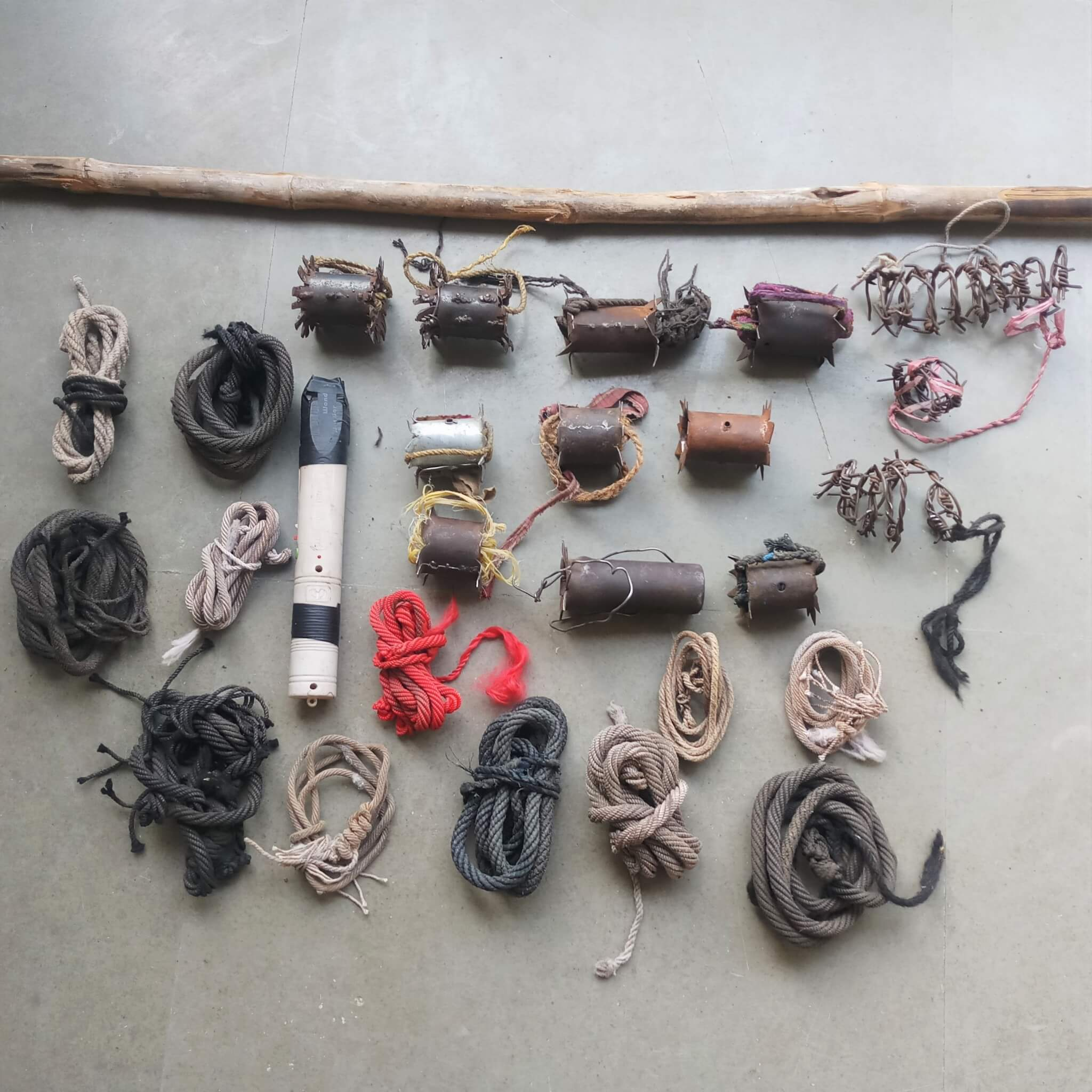 An array of cruel devices is laid out, including a stick, nose ropes, and barbed-wire and metal yoke spikes.
