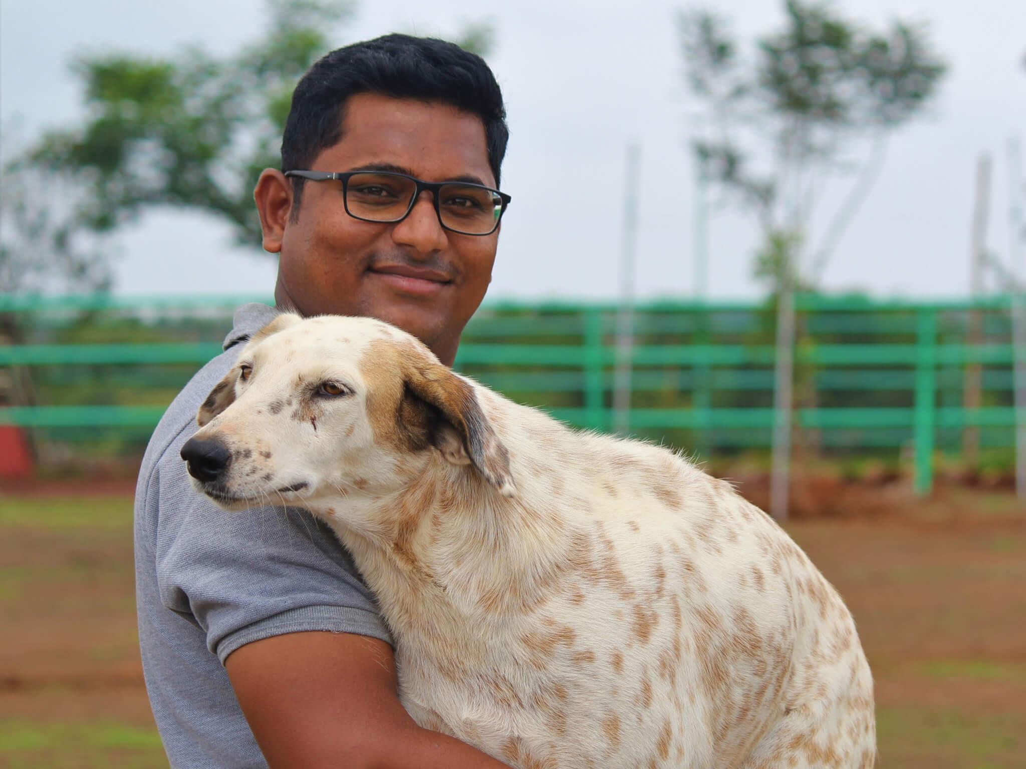 Koustubh Pol holds sanctuary resident Tommy the dog.