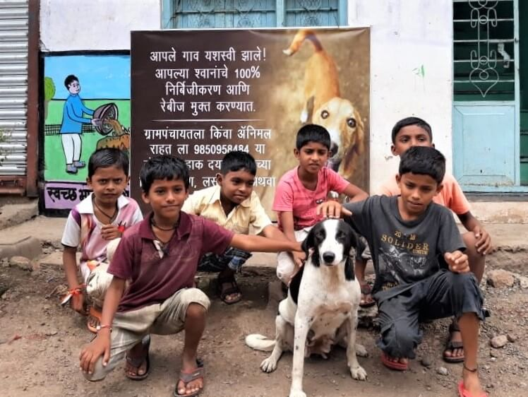 Children and one of the community's dogs smile for the camera in front of a banner announcing the village's recently earned 100% sterilization status.
