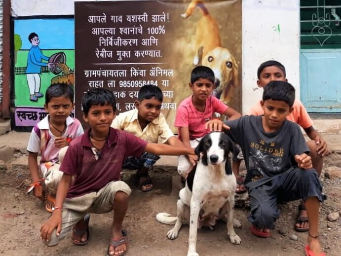 Children in Bavachi pose with a village dog in front of a banner celebrating the sterilization of 100% of the canines.