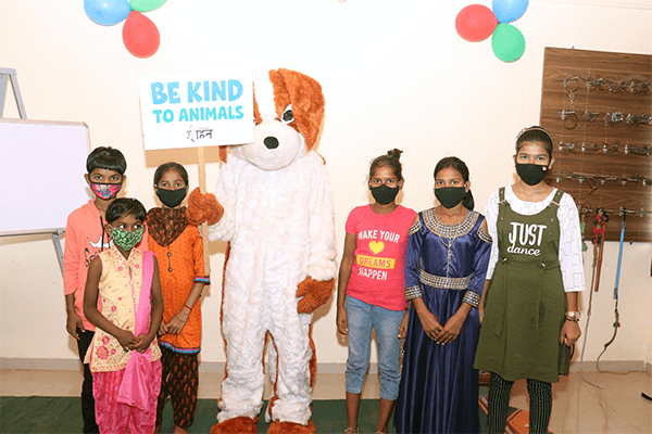 """Students at the Sangli sanctuary's education center pose with a """"dog"""" mascot."""