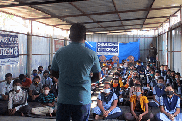 A group of students listen intently at an Animal Rahat Compassionate Citizen humane education workshop.